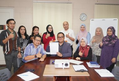 Mr. Mohamad Isham (seated, center) showing the information leaflet of the SME Skills Scheme.